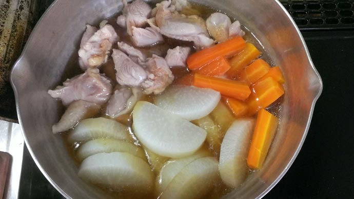 鶏もも肉の煮物に醤油を入れます。